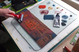 Inking up a lino block using a roller